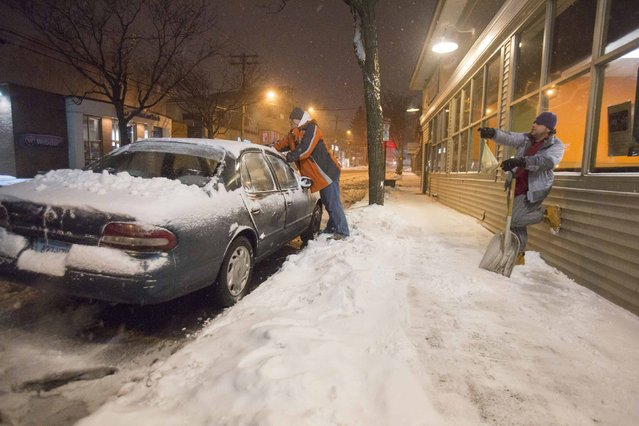 An employee of a local restaurant clears his car of snow to make return home as a statewide travel ban goes into effect in New Haven, Connecticut, January 26, 2015. A massive, wind-whipped blizzard slammed into the U.S. Northeast on Monday. (Photo by Michelle McLoughlin/Reuters)
