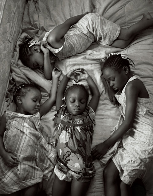 Nestled in their bed in Miami, Florida, four young sisters nap on a Sunday afternoon after attending church, December 6, 2009. (Photo by Maggie Steber/National Geographic)