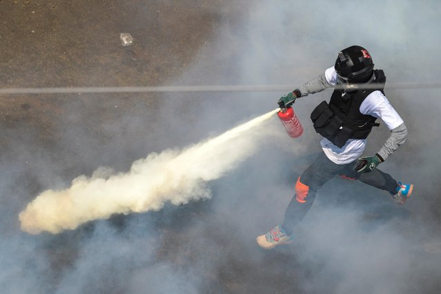 A protester sprays a fire extinguisher as demonstrators clash with riot police officers during a protest against the military coup in Yangon, Myanmar, February 28, 2021. (Photo by Reuters/Stringer)