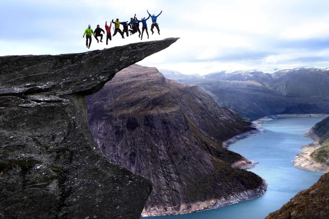 Daredevil adventurers who create their very own, potentially fatal, stunts on the tip of the Trolls Tongue in Norway, on July 16, 2013. (Photo by Caters News)