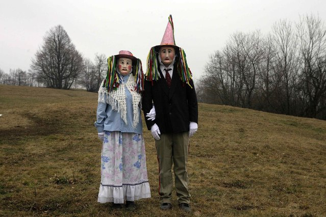 """Members of the Liski Pustje Ethnological Society wearing their native masks named """"Handsome"""" pose ahead of the Carnival in Kanal ob Soci January 14, 2015. Slovenians and members of various ethnological groups celebrate the annual carnival, also known locally as Pust, by wearing traditional masks and costumes to symbolically """"chase away"""" the winter. Prust runs from February 7 to 17 this year. (Photo by Srdjan Zivulovic/Reuters)"""