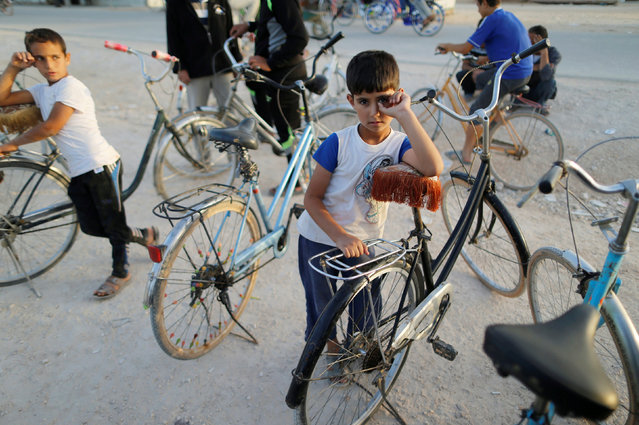 Syrian refugee children stand at a bicycles market in Al-Zaatari refugee camp near the border with Syria, in Mafraq, Jordan October 9, 2016. (Photo by Ammar Awad/Reuters)