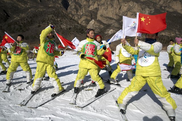 In this photo taken Friday, January 16, 2015, Chinese schoolchildren wave Chinese flags and the 2022 Olympic bid logo to show their support at the ski resort in Yanqing, a suburb of Beijing, where the speed mavens of Alpine skiing and the sliding events – bobsled, skeleton and luge – have been proposed to be held in the bid for the 2022 Winter Olympics. (Photo by Ng Han Guan/AP Photo)