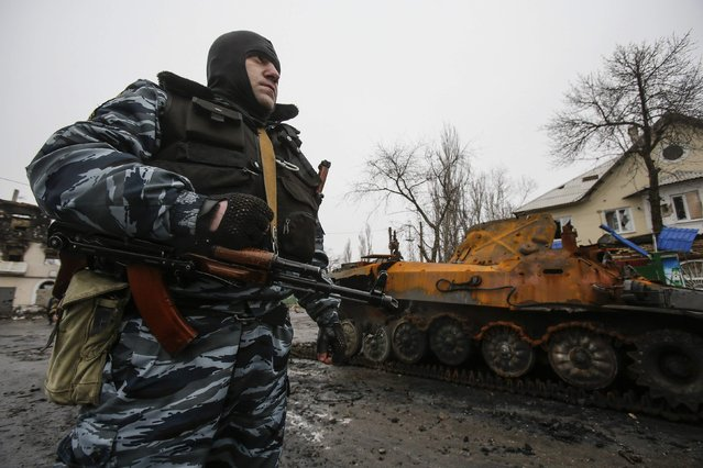 Member of the police of the separatist self-proclaimed Donetsk People's Republic stands near a burnt-out armoured vehicle in Vuhlehirsk, Donetsk region February 6, 2015. (Photo by Maxim Shemetov/Reuters)