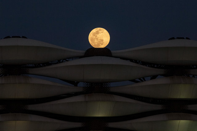 """This picture taken on March 28, 2021 shows a view of the rising full """"Worm Moon"""" above Basra International Stadium in the southern Iraqi city. (Photo by Hussein Faleh/AFP Photo)"""