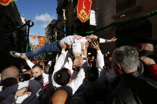 A man is lifted by colleagues during a band march at the feast marking the shipwreck of Saint Paul, Malta's patron saint, in Valletta February 10, 2015. The Maltese trace their conversion to Christianity to Saint Paul's three-month stay on the island after he was shipwrecked there in 60 A.D. (Photo by Darrin Zammit Lupi/Reuters)
