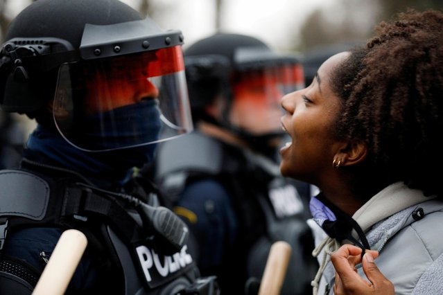 A demonstrator confronts police during a protest after police allegedly shot and killed a man, who local media report is identified by the victim's mother as Daunte Wright, in Brooklyn Center, Minnesota, U.S., April 11, 2021. (Photo by Nick Pfosi/Reuters)