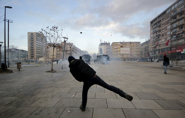 A protester throws a rock at police during clashes in Pristina, Kosovo January 9, 2016. Demonstrators in Kosovo fought running battles with police and briefly set fire to government headquarters on Saturday in the latest violence in the young Balkan country over an accord with its former ruler Serbia. (Photo by Agron Beqiri/Reuters)