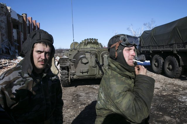 Fighters with the separatist self-proclaimed Donetsk People's Republic smoke near an armoured personnel carrier in the village of Nikishine, south east of Debaltseve, February 17, 2015. (Photo by Baz Ratner/Reuters)