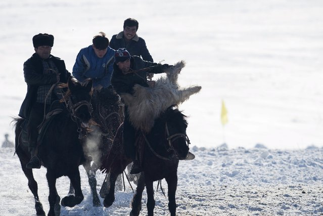 Herders ride horses as they fight for a goat during a Buzkashi game at a winter festival in Yining, Xinjiang Uighur Autonomous Region, China, January 10, 2016. (Photo by Reuters/China Daily)