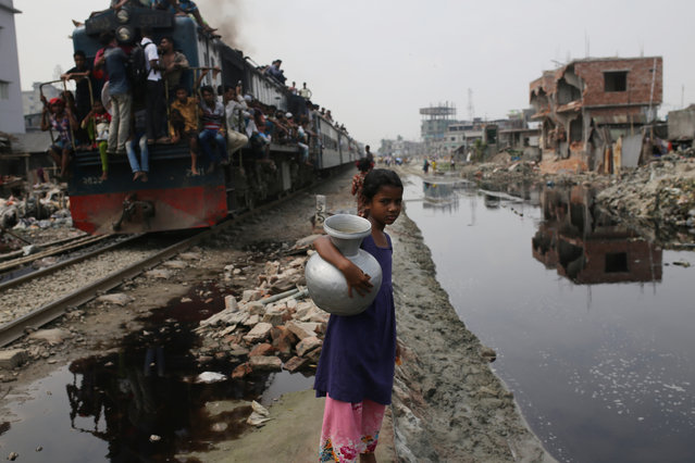A girl stands next to a railway track near a slum in Dhaka, Bangladesh on September 18, 2018. Deaths in the country due to environmental pollution and related health risks make it one of the worst affected countries in the world. (Photo by Rehman Asad/Barcroft Images)