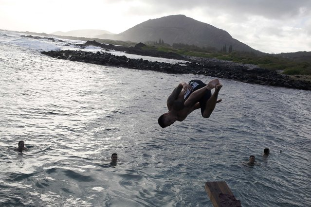 A young man does a flip into the water along the coastline near Waimanalo, Hawaii December 27, 2015. (Photo by Jonathan Ernst/Reuters)