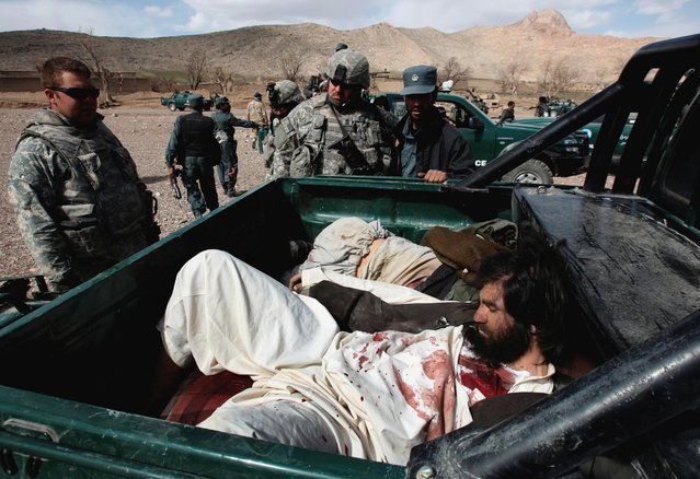 U.S Army soldiers and an Afghan policeman look at the bodies of Taliban fighters after a 40-minute gun battle near the village of Shajoy in Zabol province March 2008. (Photo by Goran Tomasevic/Reuters)