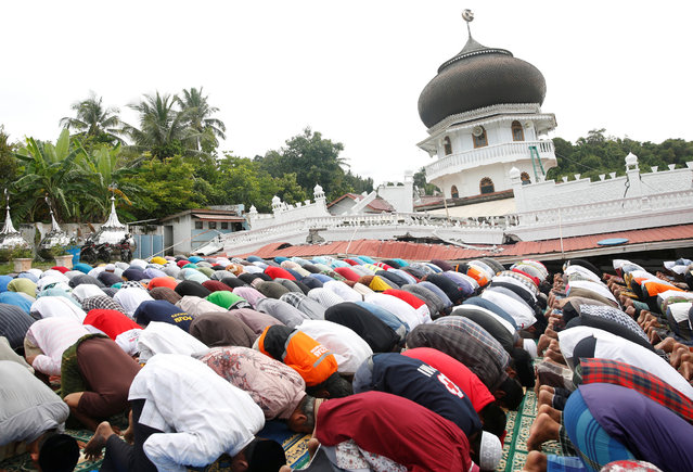 Muslims attend Friday prayers at Jami Quba mosque which collapsed during this week's earthquake in Pidie Jaya, Aceh province, Indonesia December 9, 2016. (Photo by Darren Whiteside/Reuters)