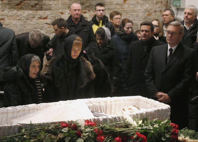 Mourners, including Dina Eidman (L), mother of Russian leading opposition figure Boris Nemtsov, Mikhail Kasyanov (R), an opposition leader and Russian former Prime Minister, and relatives and acquaintances, surround a coffin as they attend a memorial service before the funeral of Nemtsov in Moscow, March 3, 2015. Several hundred Russians, many carrying red carnations, queued on Tuesday to pay their respects to Boris Nemtsov, the Kremlin critic whose murder last week showed the hazards of speaking out against Russian President Vladimir Putin. REUTERS/Maxim Zmeyev