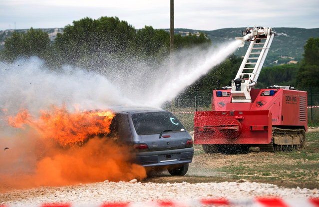 "An MVF-5 Multifunctional Robotic Firefighting System by company Dok-Ing sprays water canon as part of a TIEMS annual conference entitled ""Robotics in emergency and crisis management, use of UGVs, from Military and EOD to Civil protection"" at the Bouches-du-Rhone Fire Department school (SDIS 13) in Velaux, southern France. (Phioto by Bertrand Langlois/AFP Photo)"