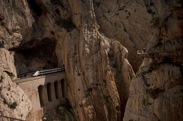 """A train passes through a tunnel in the rocks as people walk the foot-path """"El Caminito del Rey"""" (King's little path) a narrow walkway hanging and carved on the steep walls of a defile in Ardales near Malaga on March 15, 2015. (Photo by Jorge Guerrero/AFP Photo)"""