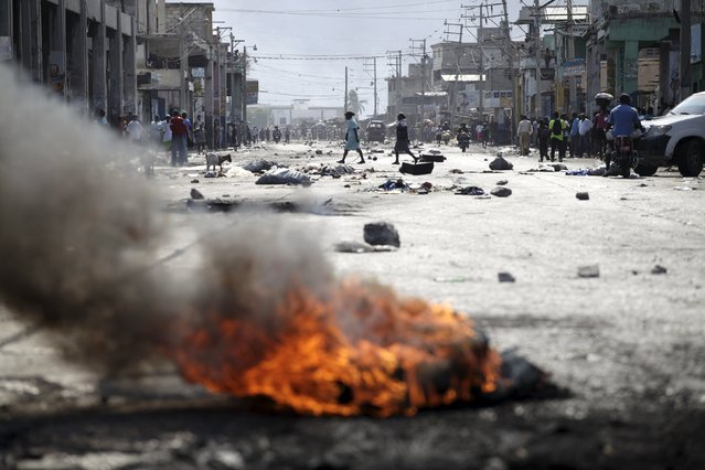 Two women cross a street blocked by rocks and a burning barricade before a demonstration against the government in Port-au-Prince, Haiti, January 24, 2016. Haiti was due to choose President Michel Martelly's replacement on Sunday, but the two-man race was postponed indefinitely after opposition candidate Jude Celestin refused to participate over alleged fraud that sparked anti-government protests and violence. (Photo by Andres Martinez Casares/Reuters)