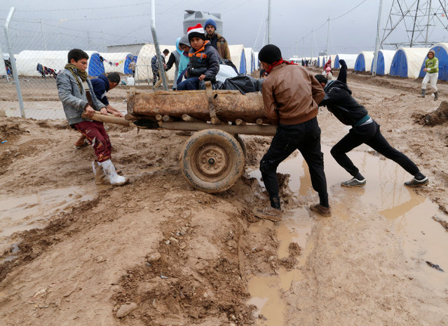 Displaced Iraqis who fled the Islamic State stronghold of Mosul, push a cart through mud following heavy rain at Khazer camp, Iraq, December 19, 2016. (Photo by Ammar Awad/Reuters)