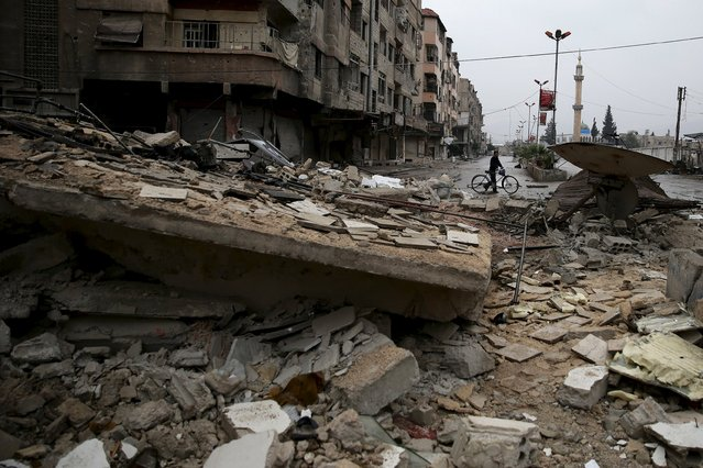A man rides a bicycle near rubble of damaged buildings in the town of Douma, eastern Ghouta in Damascus, Syria November 17, 2015. (Photo by Bassam Khabieh/Reuters)