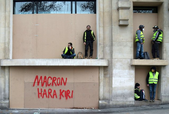 """Protestors get some rest near an inscription reading """"Macron Hara Kiri"""" during a demonstration of yellow vests (gilets jaunes) against rising costs of living they blame on high taxes in Paris, on December 8, 2018. The """"yellow vest"""" movement in France originally started as a protest about planned fuel hikes but has morphed into a mass protest against President's policies and top-down style of governing. (Photo by Zakaria Abdelkafi/AFP Photo)"""