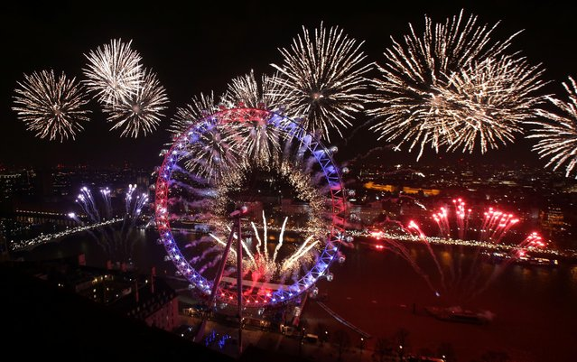 """Fireworks explode around The Elizabeth Tower, also known as """"Big Ben"""", and the London Eye during New Year' s celebrations in central London just after midnight on January 1, 2017. (Photo by Daniel Leal-Olivas/AFP Photo)"""
