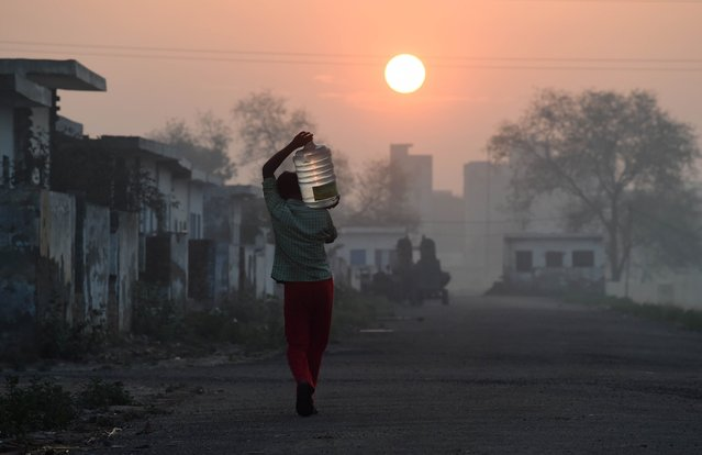 This photo taken on March 18, 2015 shows a migrant labourer carrying a bottle of water he filled from a water tanker at the camp where he and others like him live in the Dwarka sector of New Delhi on March 18, 2015. (Photo by Roberto Schmidt/AFP Photo)