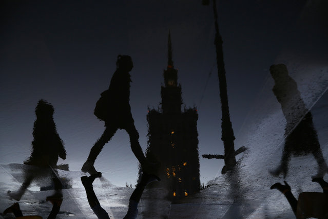 Women are reflected in a puddle as they walk in front of the Palace of Culture during rainy day in Warsaw March 4, 2015. Picture flipped 180 degrees. (Photo by Kacper Pempel/Reuters)