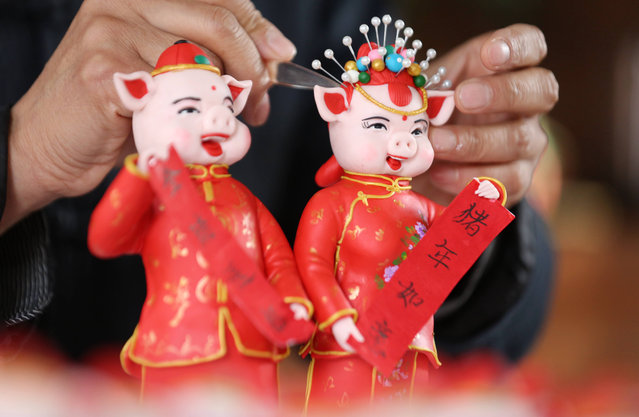 Folk artist Zuo Ansheng makes dough figurines of pigs holding couplets to greet the Year of the Pig on January 8, 2019 in Linyi, Shandong Province of China. Chinese New Year also known as the Spring Festival is China's most important festival and holiday. Chinese New Year 2019 falls on February 5 according to the Lunar calendar. It is a Year of the pig, which occupies the 12th positions in the 12-year cycle of Chinese zodiac animal signs. (Photo by Wang Yanbing/VCG via Getty Images)