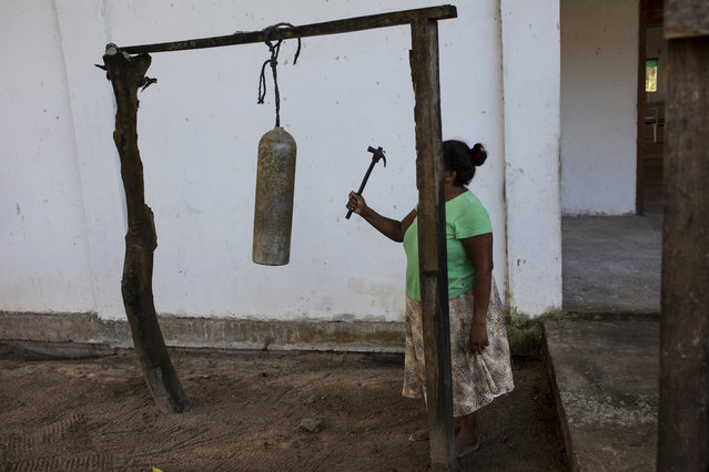 In this February 11, 2018 photo, Elvira Mendoza Espinosa, hits a diving tank with a hammer announcing the start of the morning Mass, outside the Moravian church in Kaukira, Honduras. In the Mosquitia, diving permeates everyday life, as it does in Kaukira, one of the villages on the Mosquitia. (Photo by Rodrigo Abd/AP Photo)
