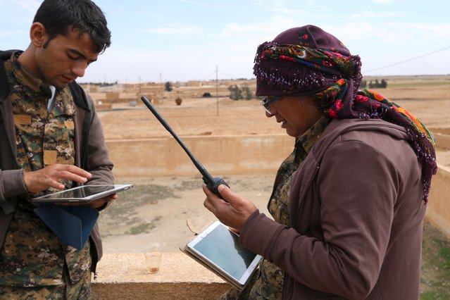 A Syria Democratic Forces leader (R) uses a walkie talkie and a tablet to communicate with the U.S. alliance operation room on the outskirts of al-Shadadi town, Hasaka countryside, Syria February 19, 2016. (Photo by Rodi Said/Reuters)