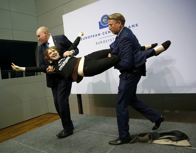 Security officers detain a protester who jumped on the table in front of the European Central Bank President Mario Draghi during a news conference in Frankfurt, April 15, 2015. (Photo by Kai Pfaffenbach/Reuters)