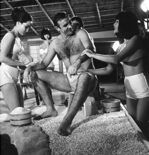 In this file photo dated September 26, 1966, British actor Sean Connery, being given a Japanese bath, during filming of a scene in the James Bond film, You Only Live Twice, at Pinewood Studios near London. The actresses shown are Yasuko Nagazuni, at left and Yee Wah Yang at right. Scottish actor Sean Connery, considered by many to have been the best James Bond, has died aged 90, according to an announcement from his family. (Photo by Sidney Smart/AP Photo)