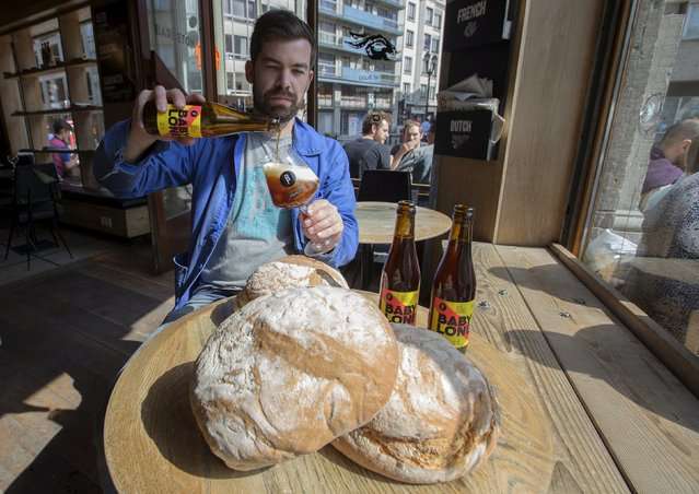 Sebastien Morvan, one of the founders of microbrewery Brussels Beer Project, displays bread and serves a beer called Babylone at Barbeton bar in central Brussels April 14, 2015. A small Brussels-based brewery has embarked on a project to make beer, the Babylone, from leftover bread, reducing a significant source of food waste and harking back to antiquity, when bread, rather than barley, was the main ingredient. (Photo by Yves Herman/Reuters)