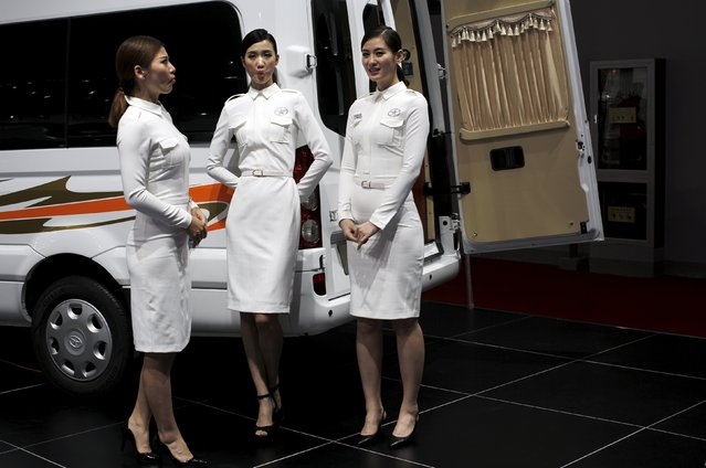 Models stand next to a JAC car vehicle during the 16th Shanghai International Automobile Industry Exhibition in Shanghai, April 20, 2015. Amid the razzmatazz, music and crowds at the Shanghai autoshow on Monday, hundreds of attractive young women, and men, mingled among the stands and company booths, introducing the newest sedans and handing out pamphlets. (Photo by Carlos Barria/Reuters)