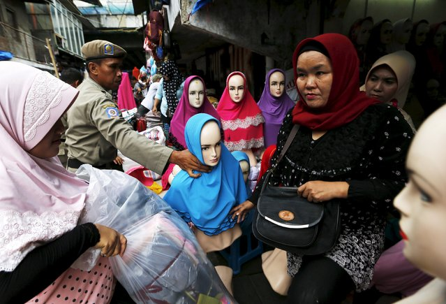 A hijab vendor (L) gathers her belongings as a Civil Service policeman (2nd L) moves her manequin near a customer (R) during a sweep operation on illegal steet vendors, causing traffic congestion at Tanah Abang market in Jakarta, April 7, 2015. (Photo by Reuters/Beawiharta)