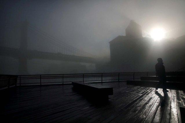 A man walks on a Brooklyn promenade near the Manhattan Bridge. (Photo by Spencer Platt/Getty Images)