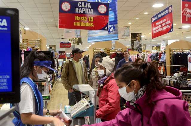 People, wearing surgical masks to protect themselves against ash from Calbuco volcano, buy groceries at a supermaket in the Patagonian Argentine area of San Marin de Los Andes April 22, 2015. (Photo by Patricio Rodriguez/Reuters)