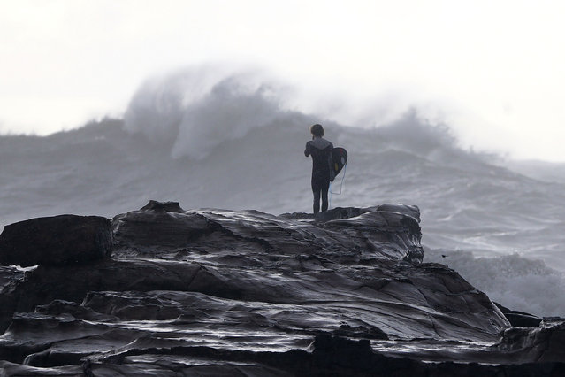 A surfer watches turbulent seas at Avoca Beach on the Cntral Coast on April 22, 2015 in Sydney, Australia. Three people have died and more than 200,000 are still without power as cyclonic winds and rains continue to lash the Sydney, Hunter Valley and Central Coast regions of New South Wales. (Photo by Tony Feder/Getty Images)