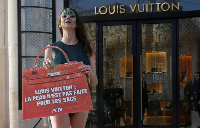 """A woman from the animal rights activist group People for the Ethical Treatment of Animals (PETA) holds a placard with the message, """"Animal skins are not for handbags"""" as she demonstrates outside of the French luxury group Louis Vuitton's store in Paris, France, January 26, 2017. (Photo by Jacky Naegelen/Reuters)"""