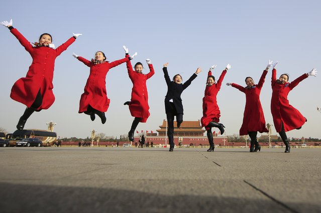 Hotel guides jump as they pose for pictures outside the Great Hall of the People during the opening session of the National People's Congress (NPC) in Beijing, China, March 5, 2016. (Photo by Aly Song/Reuters)