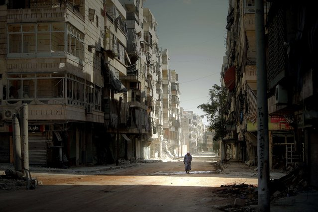 A Syrian man holds his robe while walking in the partially destroyed Salaheddin neighbourhood of Aleppo, under the control of teh Syrian army on September 3, 2012. (Photo by Joseph Eid/AFP Photo)