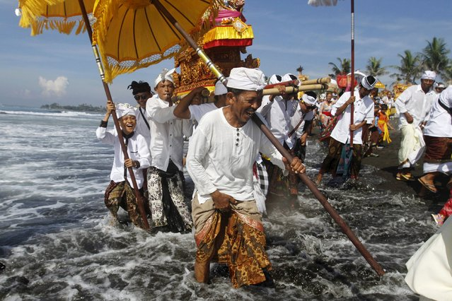 Balinese Hindus carry Pratimas, or symbols of God, on the beach during Melasti, a purification ceremony, ahead of the holy day of Nyepi, in Gianyar on the Indonesian resort island of Bali, March 6, 2016. Nyepi is a day of silence to celebrate the Balinese new year, reserved for self-reflection, where people are not allowed to use lights, light fires, work, travel or enjoy entertainment. (Photo by Roni Bintang/Reuters)