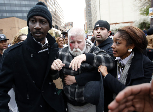 Two people assist a man who was injured and has blood on his face after a march to City Hall for Freddie Gray, Saturday, April 25, 2015 in Baltimore. (Photo by Alex Brandon/AP Photo)