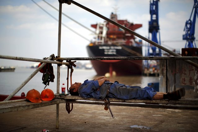 "A labourer rests during a lunch break at the Hudong-Zhonghua Shipbuilding company's shipyard in Shanghai in this October 14, 2013 file photo. China aims to lay off 5-6 million workers from ""zombie enterprises"" over the next two to three years as part of efforts to curb industrial overcapacity and pollution, two sources with ties to the country's leadership said. (Photo by Carlos Barria/Reuters)"