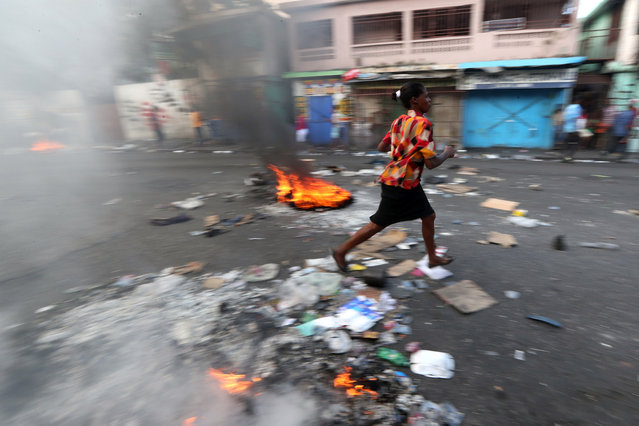 A woman walks past a burning barricade during anti-government protests in Port-au-Prince, February 17, 2019. (Photo by Ivan Alvarado/Reuters)