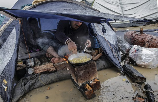 A refugee prepares food in front of his tent at a camp at the border between Greece and the Former Yugoslav Republic of Macedonia (FYROM), near Idomeni, northern Greece, 10 March 2016. After Slovenia, Croatia, Serbia and Macedonia have sealed their borders to the migration flow, tens of thousands of people are left stranded in Greece, where most migrants enter the European Union to continue on to wealthier countries in Northern Europe. (Photo by Valdrin Xhemaj/EPA)