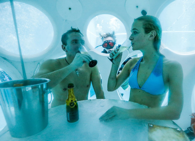 """Belgians Florence Lutje Spelberg and Nicolas Mouchart drink champagne while sitting inside """"The Pearl"""", a spheric dining room placed 5 metres underwater in the NEMO33 diving center, one of the world's deepest pools (33 metre/36 yards) built to train professional divers, before enjoying a meal inside, in Brussels, Belgium January 30, 2017. (Photo by Yves Herman/Reuters)"""