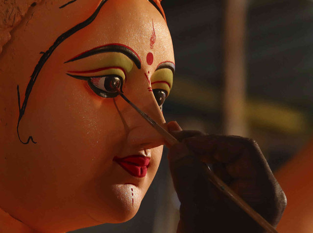 An artisan prepares an idol of Hindu goddess Durga ahead of the Hindu religious festival season in Hyderabad, India, Tuesday, October 5, 2021. (Photo by Mahesh Kumar A./AP Photo)