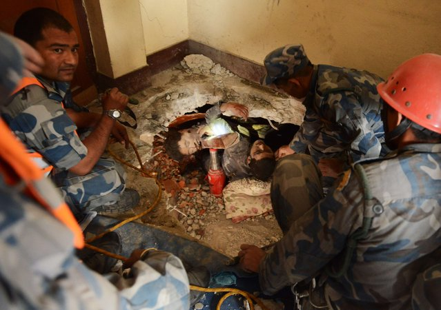 Nepalese rescue personnel rescue a trapped earthquake survivor (C/R) as his friend lies dead next to him following an earthquake in Swyambhu in Kathmandu on April 26, 2015. (Photo by Prakash Mathema/AFP Photo)